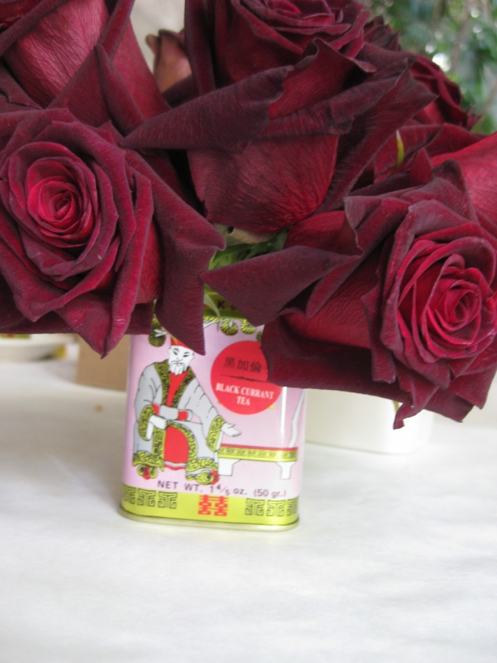 deep red roses in a pink tea tin