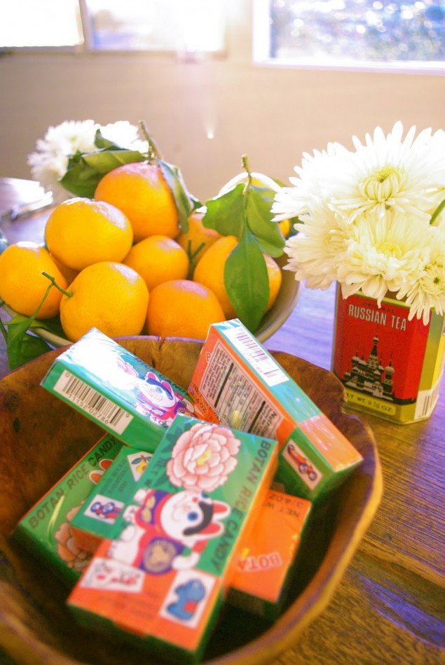 satsumas, candies annd flowers in tea tins